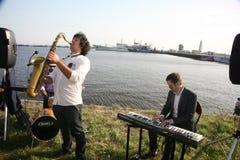 Grupo de músicos de la calle en el fondo del golfo de Finlandia en el puerto civil de Kronstadt Fotos de archivo libres de regalías