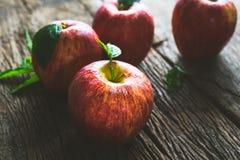 grupo de maçã vermelha na tabela de madeira, fundo vermelho da maçã para o bom imagens de stock