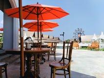 Grupo de madeira da tabela e da cadeira, sala de estar com uma vista do guarda-chuva vermelho foto de stock royalty free