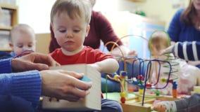 Grupo de madres y de niños que juegan con los juguetes metrajes