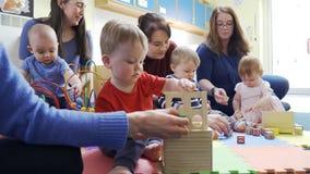 Grupo de madres y de niños que juegan con los juguetes almacen de metraje de vídeo