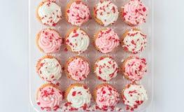 Grupo de magdalenas con helar rosado y blanco en el top Imagen de archivo