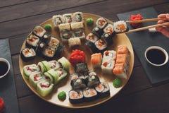 Grupo de maki e de rolos do sushi na madeira rústica preta imagem de stock royalty free