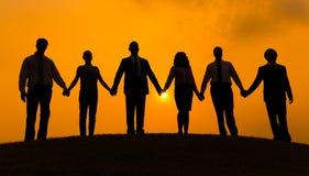 Grupo de mano del control del socio comercial junto en silueta con el fondo de la salida del sol foto de archivo