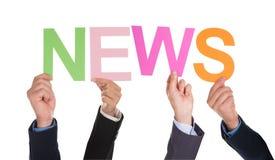 Grupo de manos de los empresarios que llevan a cabo noticias de la palabra Imágenes de archivo libres de regalías