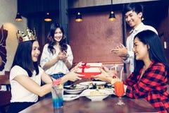 Grupo de manos que aplauden de la gente asiática para felicitarse para el regalo o las recompensas de cumpleaños durante cena imagen de archivo libre de regalías
