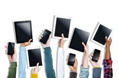 Grupo de manos que llevan a cabo los dispositivos de Digitaces Imagen de archivo