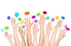 Grupo de manos étnicas multi diversas que alcanzan para las burbujas del discurso Foto de archivo