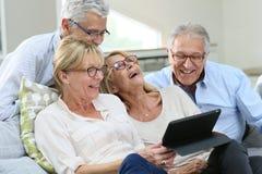 Grupo de mayores que ríen y que usan la tableta Imagen de archivo libre de regalías