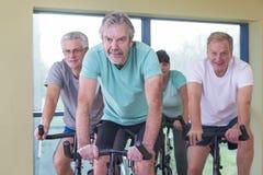 Grupo de mayores que usan las bicis de giro Fotos de archivo libres de regalías