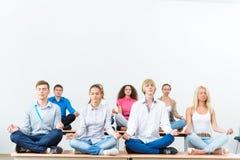 Grupo de meditar de la gente joven fotos de archivo libres de regalías