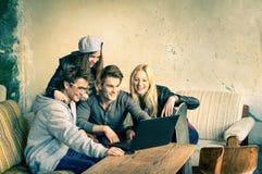 Grupo de mejores amigos jovenes del inconformista con el ordenador portátil del ordenador