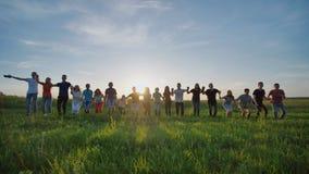 Grupo de melhores amigos e de estudantes que saltam fora Por do sol com raios da luz do sol filme