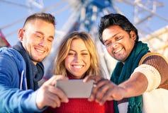 Grupo de melhores amigos multirraciais que tomam um selfie imagem de stock