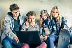 Grupo de melhores amigos novos do moderno com computador Fotos de Stock Royalty Free