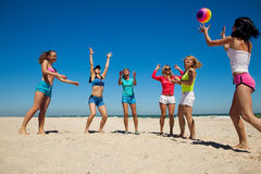 Grupo de meninas alegres novas que jogam o voleibol Fotografia de Stock Royalty Free