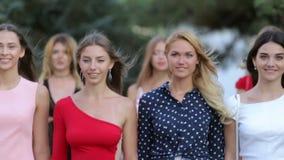 Grupo de meninas bonitas nos vestidos que vêm ao longo do parque filme