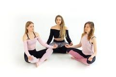 Grupo de meninas bonitas novas de três pessoas que fazem o namaste da ioga com olhos fechados fotografia de stock
