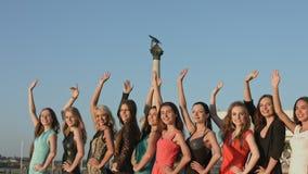 Grupo de meninas bonitas que estão na fileira, rindo e acenando com suas mãos vídeos de arquivo