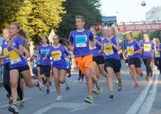 Grupo de meninas e de meninos running em uma curva Imagem de Stock Royalty Free