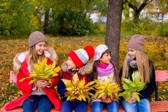 Grupo de meninas no parque do outono no brench Imagens de Stock