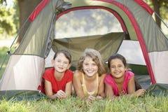 Grupo de meninas que têm o divertimento na barraca no campo imagens de stock royalty free