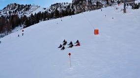 Grupo de meninos e de snowboarders das meninas que sentam-se na neve Fotografia de Stock Royalty Free