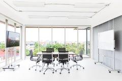 Grupo de mesa de reuniones y de sillas en los wi blancos y anchos de la oficina imagenes de archivo