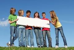 Grupo de miúdos com sinal em branco fotos de stock royalty free