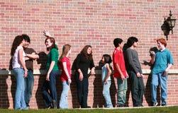 Grupo de miúdos pela parede de tijolo Foto de Stock