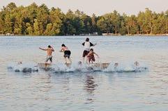 Grupo de miúdos que saltam no lago foto de stock royalty free