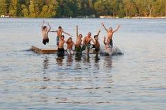 Grupo de miúdos que saltam no lago Fotografia de Stock