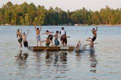 Grupo de miúdos que saltam no lago Fotos de Stock Royalty Free