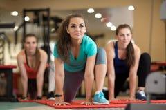 Grupo de moças que fazem exercícios no gym foto de stock