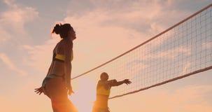 Grupo de moças que jogam o voleibol de praia durante o por do sol ou o nascer do sol, movimento lento, vídeos de arquivo