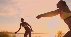 Grupo de moças que jogam o voleibol de praia durante o por do sol ou o nascer do sol, movimento lento, filme