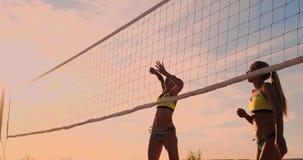 Grupo de mo?as que jogam o voleibol de praia durante o por do sol ou o nascer do sol video estoque
