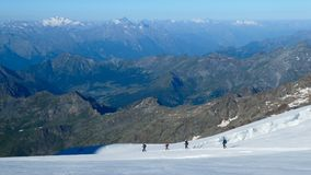 Grupo de montañeses que descienden en el glaciar imagen de archivo