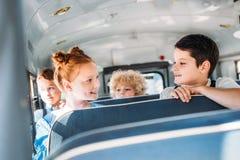 grupo de montada pequena feliz dos alunos fotografia de stock royalty free