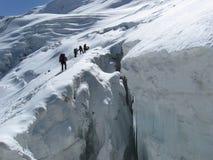 Construindo uma ponte sobre o pico Lenin da geleira da rachadura Foto de Stock