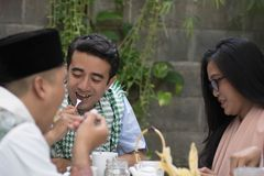 Grupo de muçulmano novo feliz tendo o jantar exterior durante ramadan fotos de stock