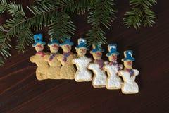 Grupo de muñeco de nieve del pan de jengibre en una tabla de madera Fotos de archivo