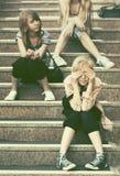 Grupo de muchachas adolescentes felices que se sientan en pasos Imágenes de archivo libres de regalías