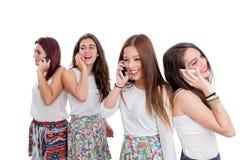 Grupo de muchachas adolescentes que hablan en los teléfonos elegantes Fotos de archivo libres de regalías