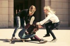 Grupo de muchachas adolescentes que juegan con el monopatín Foto de archivo libre de regalías