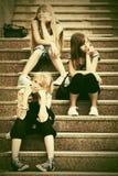 Grupo de muchachas adolescentes que se sientan en pasos Fotos de archivo libres de regalías