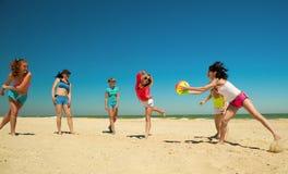 Grupo de muchachas alegres jovenes que juegan a voleibol Imagenes de archivo