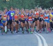 Grupo de muchachas corrientes y de muchachos que corren en el camino Imagen de archivo libre de regalías