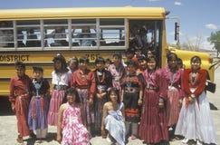 Grupo de muchachas del nativo americano en el traje que se coloca delante del autobús escolar en el sombrero mexicano, UT meridio Fotografía de archivo