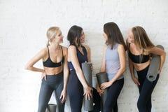Grupo de muchachas deportivas jovenes con hablar de las esteras de la yoga fotos de archivo libres de regalías